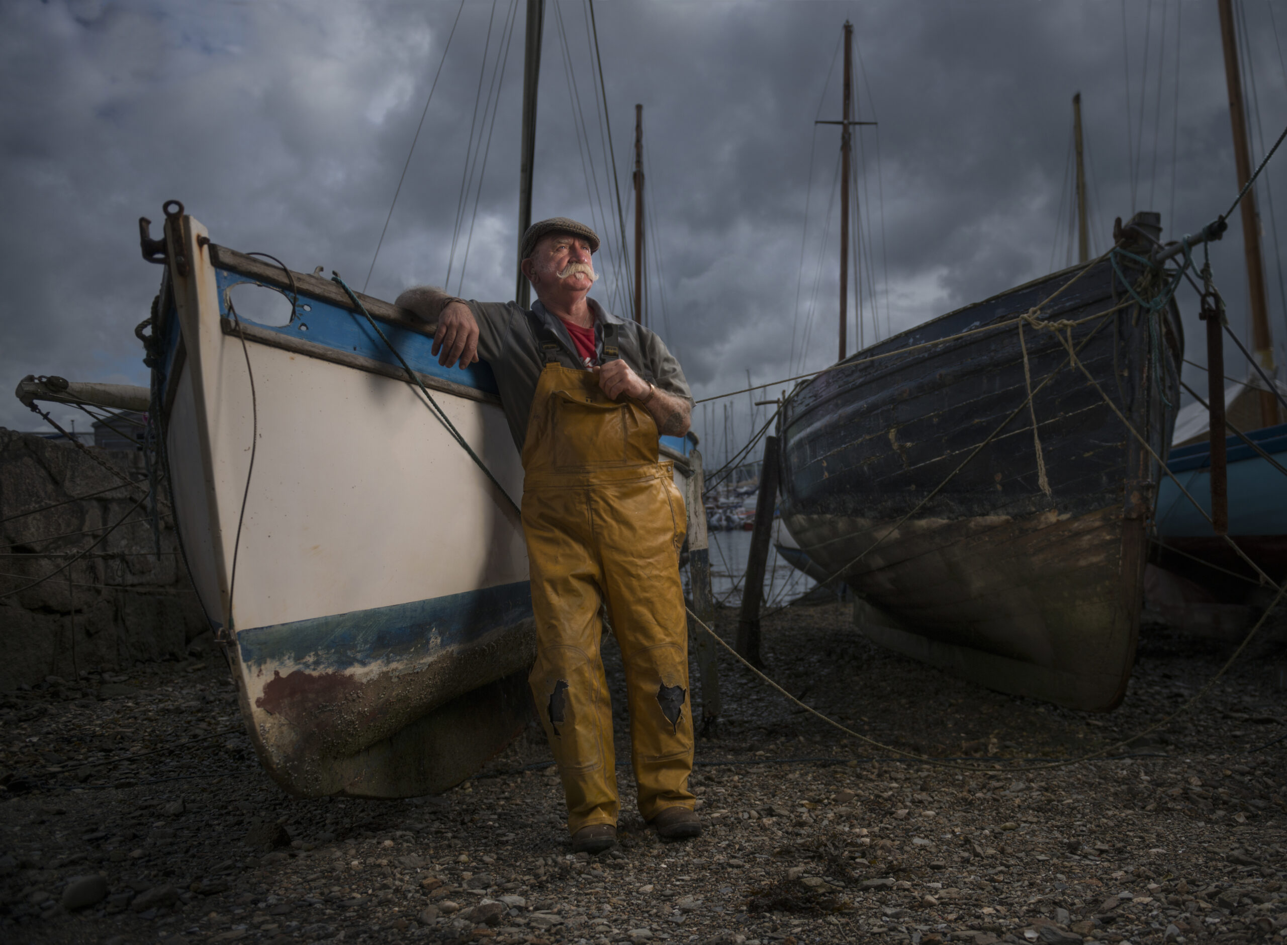 Oyster fisherman in cornwall standing proud against his old boat